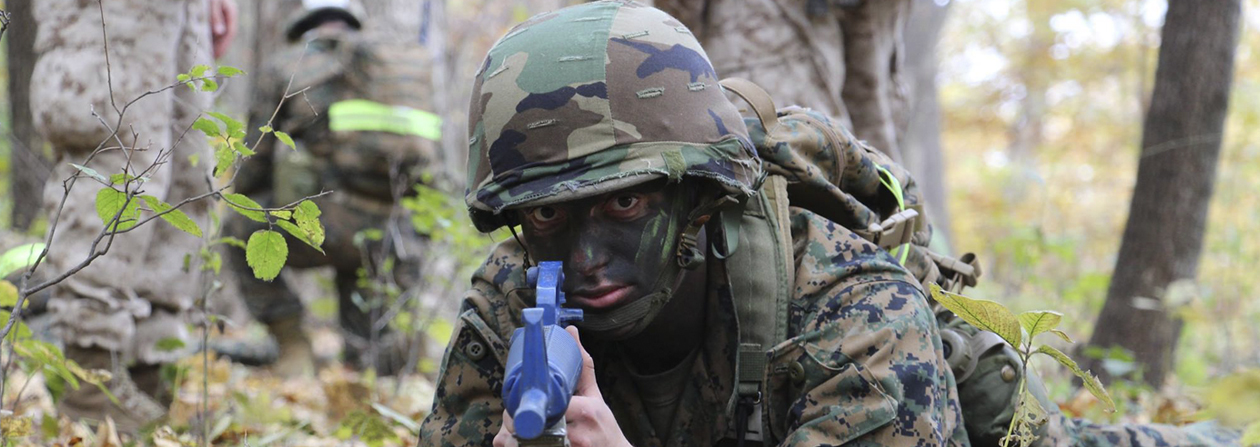 Marine in camo pointing practice weapon